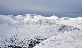 A winter snowy Lake District scene of Helvellyn, Striding Edge and Catstye Cam from Rampsgill Head near Hartsop.