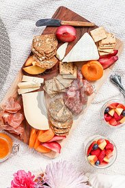 Seasonal picnic charcuterie and cheese board with crackers and fresh fruit