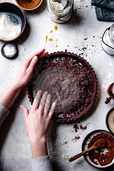 Hands preparing a chocolate tart crust.
