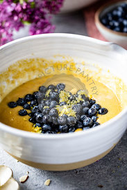 A cake mixture in a bowl with blueberries