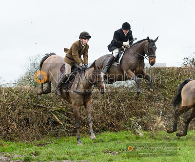 Ned Hercock, Richard Clowes jumping a hedge near Leicester Lane. The Cottesmore and Fernie Hunts at Hill Top 10/12