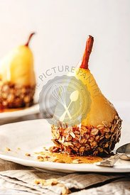 Poached pear coverd with chocolate and home-made granola, on a withe plate with syrup drizzled on top.