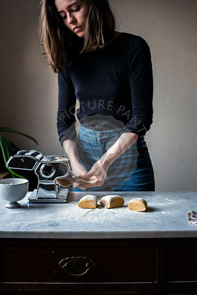Woman Making Fresh Pasta in a kitchen