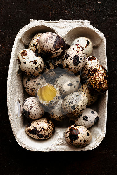 Broken quail egg and a group of eggs into a carton