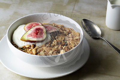 Healthy breakfast of muesli, yoghurt and sliced figs.