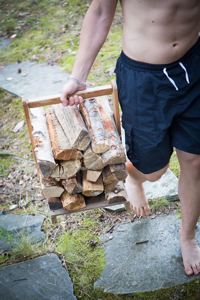 Nuori mies kantamassa puita saunalle|||Young man carrying a wood for heating up a sauna