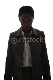 A tough woman, standing and looking at camera, in semi-silhouette – shot from eye level.