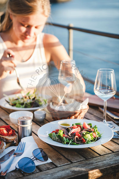 Young woman having meal in cafe with view in Italy