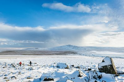 Walkers descend from White Tor, in winter, Great Mis Tor and North Hessary Tor beyond, Dartmoor, Devon - BP7193