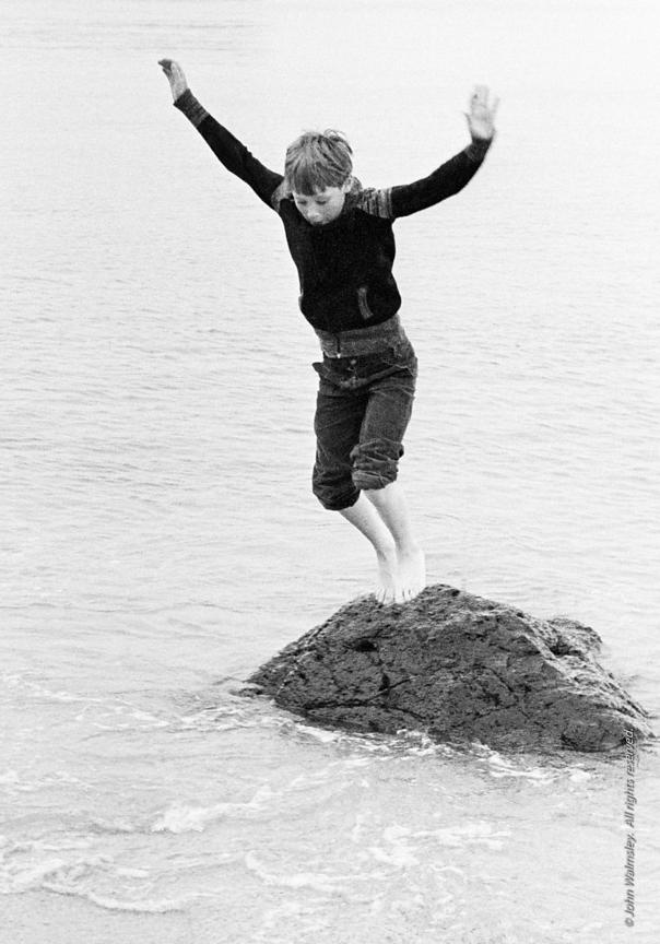 #75769  Leaping from a rock.  One of the kids from Wester Hailes on a visit with Youth Workers to the beach near Dunbar, East...