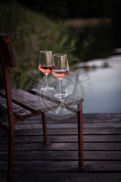 Glass of rose wine on a table by a lake