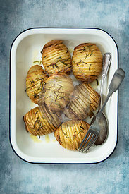 Crispy roasted hasselback potatoes in a serving dish.