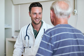 Smiling male doctor talking to older male patient