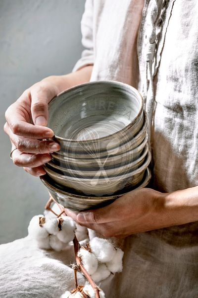 Woman in cotton dress hold in hands set of empty craft ceramic bowls cover by grey texture glaze and cotton flowers.