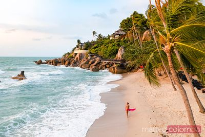 Asian woman walking on beach at sunrise, Ko Samui, Thailand