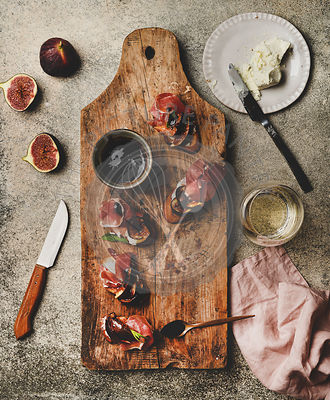 Crostini with prosciutto and glass of wineon wooden board
