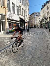 Brussels, Belgium, April 25, 2020 - .Rue marché aux herbes, a family cyclists on a deserted street in the old quarter of Brus...