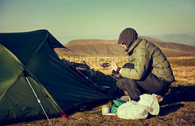 A female hiker preparing a stove to make a hot drink beside their tent that's pitched on a mountain summit at sunrise at Ramp...