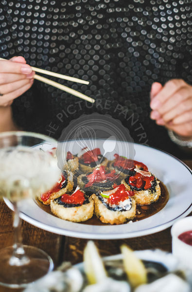Girl eating baked susi maki with chopsticks at Japanese rstaurant