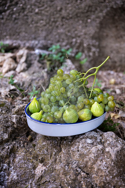 Fresh grapes and figs in the ceramic bowl outside in the garden