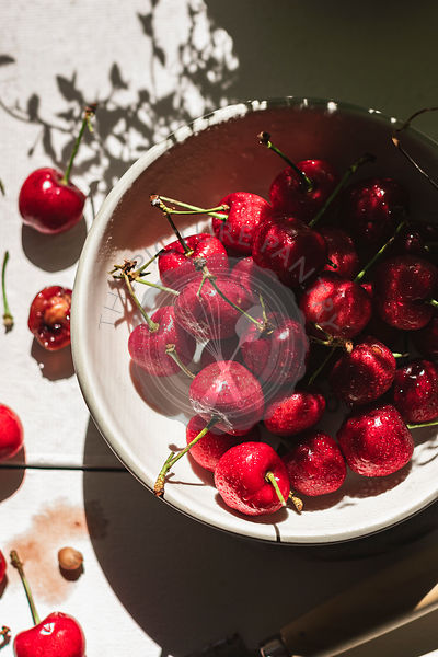 Cherries in a bowl and scattered on a white table