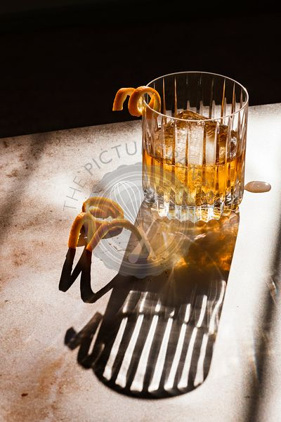 Whiskey in a rocks glass in hard light with orange spirals.