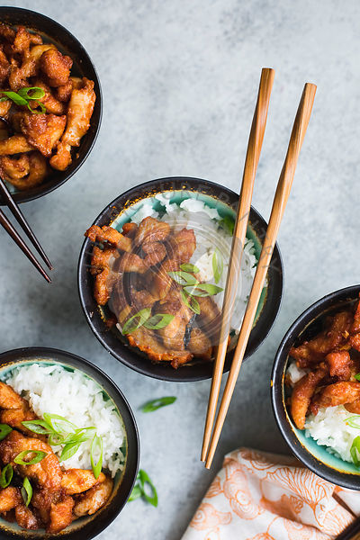 Asian style chicken in bowls with rice and chopsticks