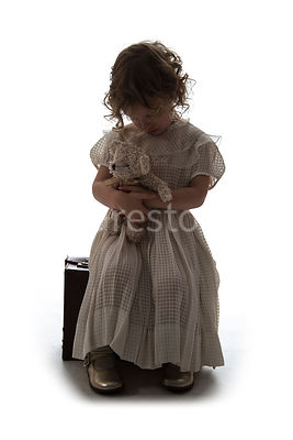 A semi-silhouette of a litle girl sitting on a suitcase – shot from mid level.