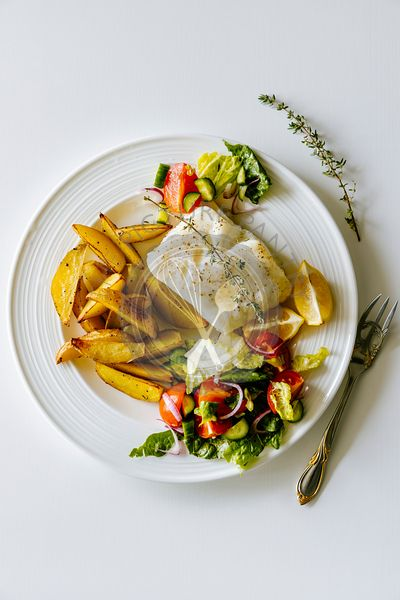 Oven baked chilean sea bass with herb roasted potatoes and fresh salad