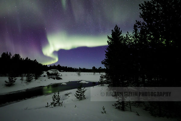Aurora above a small cottage near a freezing stream in Finnish Lapland