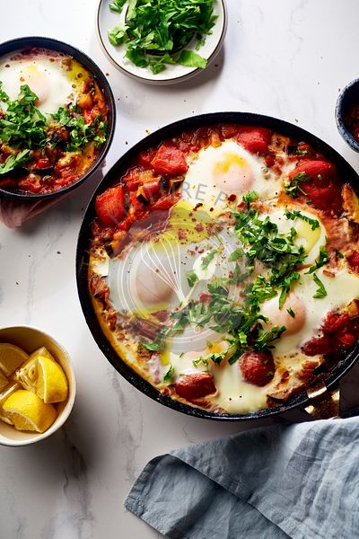 Shakshuka with vegetables, herbs, tomato sauce and grilled bread slices