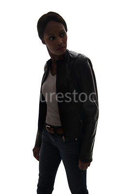 A tough woman, in a leather jacket, in semi-silhouette – shot from eye level.