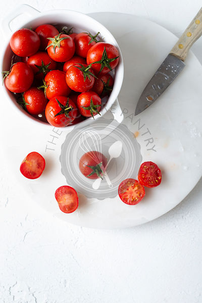 Freshly washed cherry tomatoes in a white colander, prepared for slicing. Overhead view.