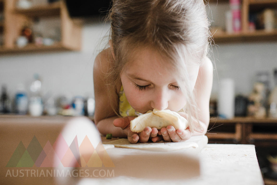 Little girl smelling freshly prepared stuffed pastry