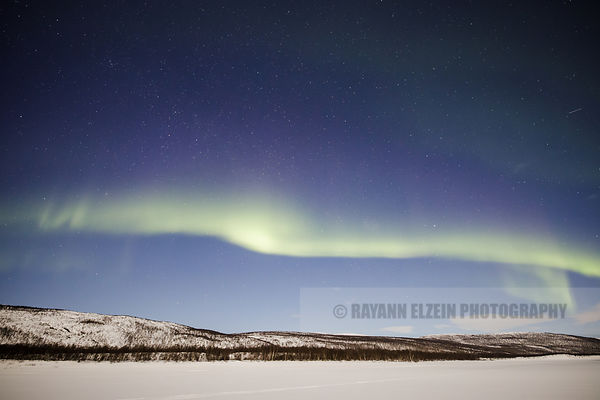 Aurora band above the fells as seen from the shore of the Teno River in Utsjoki, Finnish Lapland