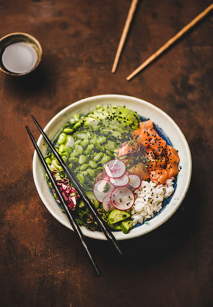 Healthy salmon poke bowl with vegetables, greens, rice, soy sauce