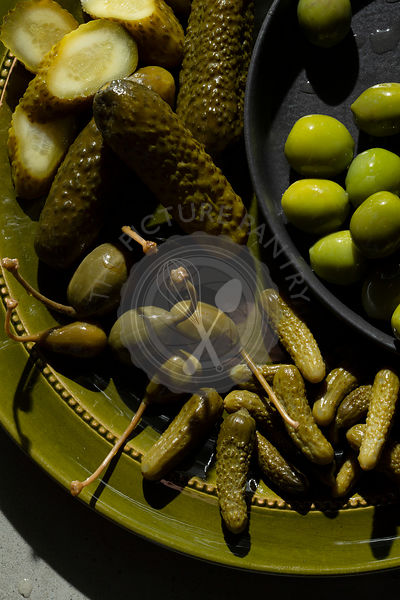A selection of pickled gherkins, caper berries and green olives on an olive green plate.