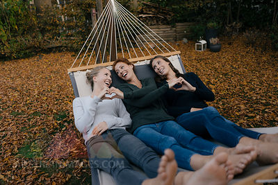 Happy mother with two teenage girls lying in hammock in garden in autumn