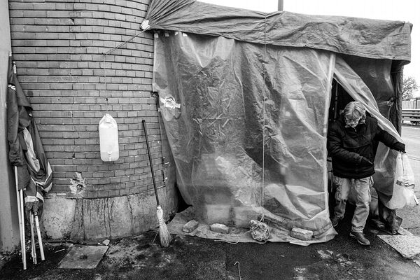 "Massimo exiting the makeshift shelter for a cigarette. On the left, metal workers' union flags and a ""water point""."