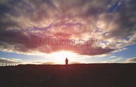 A distant hiker in the centre of the frame walking into a dramatic sunset.