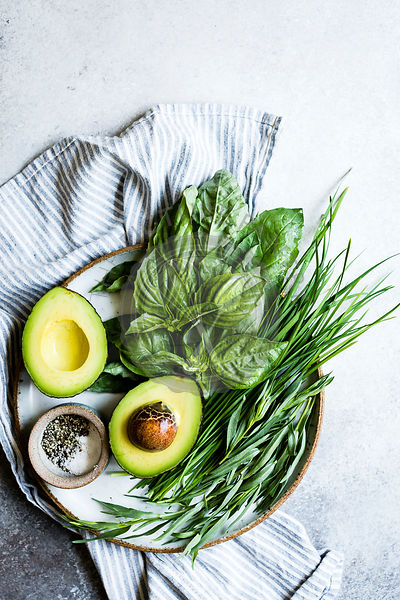 Avocado and herbs on a plate, with copy space