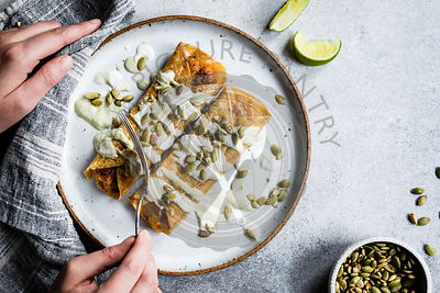 Cheesy pumpkin taquitos with roasted jalapeno pepita crema