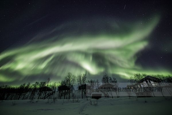 Strong Aurora above typical Finnish cottages in Utjsoki in Lapland