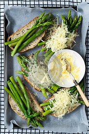 Asparagus spears and grated cheese on wholegrain sourdough bread.