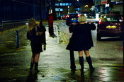 Prostitutes Sarah and Vicky (longer hair) waiting for clients at a North London street corner.