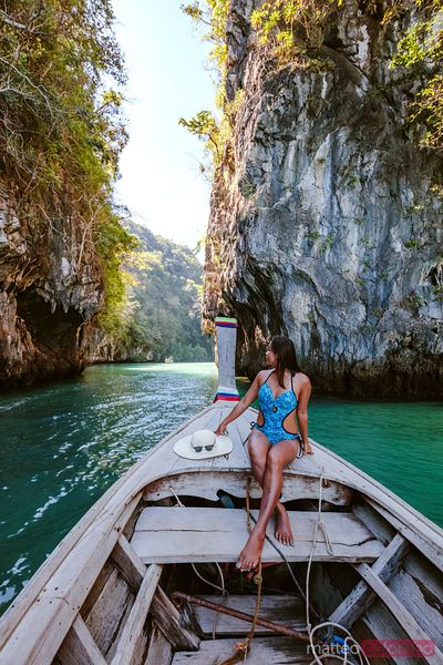 Young woman on longtail boat prow, Hong island, Thailand