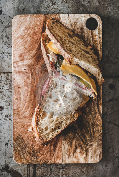 Flat-lay of pastrami sandwich slices in sourdough bread with cheese