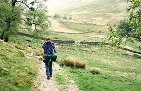 A female hiker, backpacker, walking along a mountain trail in the English Lake District.
