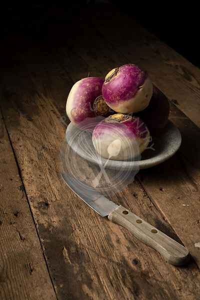 Raw turnips in a bowl on a rustic wooden surface. A wooden handled knife is beside them.