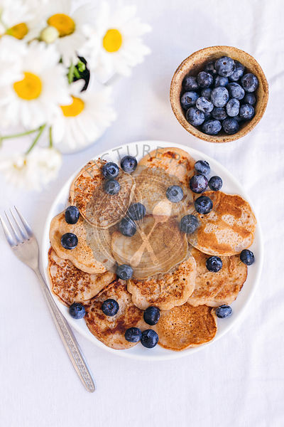 Pancakes with fresh blueberries served on a white ceramic plate